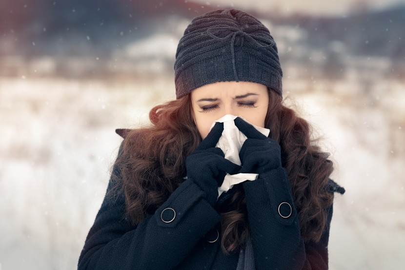 Suffering ill girl with flue being cold holding paper napkin in wintertime